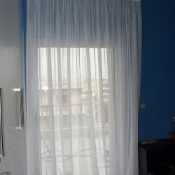 Απόλυτη αντίθεση του λευκού πάνω σε μπλε σκούρο τοίχο. Κουρτίνα από ημιδιάφανη λευκή γάζα.