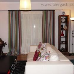 Κουρτίνα σαλονιού με ρίγες με λινή γάζα για εσωτερικό. Με ασορτί διακοσμητικά μαξιλάρια στον καναπέ.