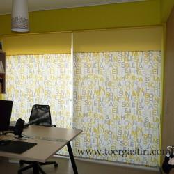 Ρόλλερ σε τζαμαρία με κίτρινα και γκρι γράμματα και κίτρινη φάσα στο πάνω μέρος.